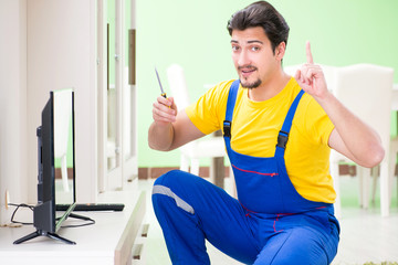 Male professional serviceman repairing tv at home