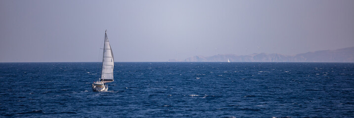 Race of two sailboats with wind help, in calm sea. Blue sky and mountains background, banner.