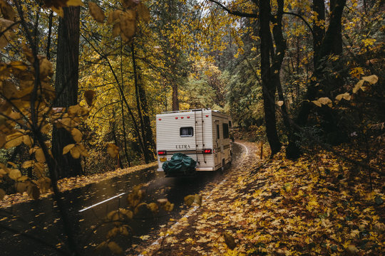 Camper drives through the wet autumn forest