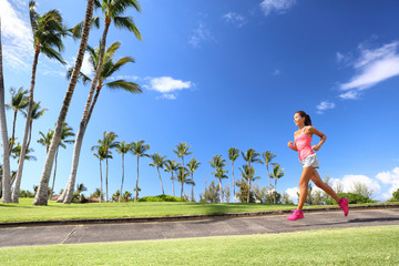 Girl jogging in park living an active summer. Runner woman running on sidewalk, healthy lifestyle.