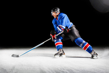 Hockey player with stick turning around skating on ice against black background