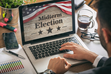 Businessman with a US of America midterm elections picture onscreen