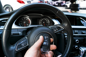 Man's hand holding a wireless car key in black leather interior. Modern Car interior details. Car detailing. Car inside. Car detailing