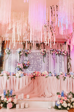 Richly decorated with flowers and fabrics reception for a wedding Banquet. Pastel pink colors