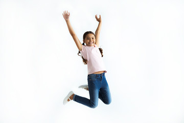 The little girl jumping on the white wall background