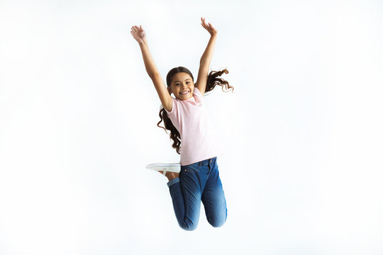 The happy girl jumping on the white wall background