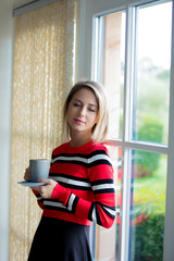 Young girl with cup of coffee stay near window at home. Autumn season
