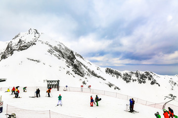 Winter landscape. Snow covered high mountain peaks under cloudy panoramic skies in Europe. People engage winter extreme sports. Downhill skiers and snowboarders.