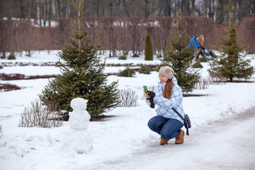 Woman takes picture of snowman on cellphone in park in winter season