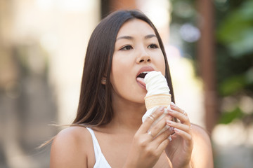 Happy young smiling asian brunette woman eating ice cream on green trees background in Park