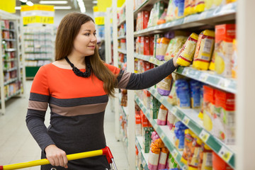 Caucasian young woman with shopping cart selects cereals on store counter