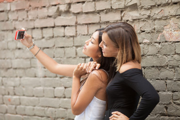 Two young female friends taking a picture of themselves on a smart phone. Selfie.