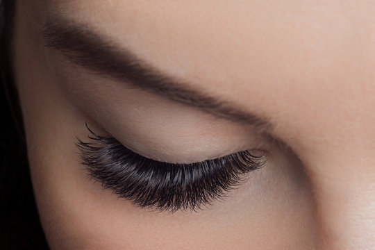 Woman with long lashes in beauty salon. Concept eyelash extension procedure.
