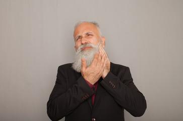 Portrait of bearded senior man having terrible toothache