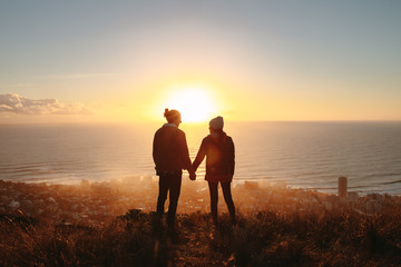 Traveling couple on cliff at sunset
