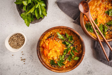 Yellow Indian vegan lentil soup curry with parsley and sesame in a wooden bowl.