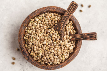 Wooden bowl of untreated hemp seeds. White background, top view.