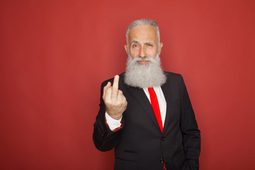 Old bearded businessman showing fuck sign at camera and smiling. Business people concept, richly and success. Indoor, studio shot on red background