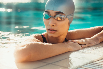 Female swimmer relaxing at the edge of a swimming pool