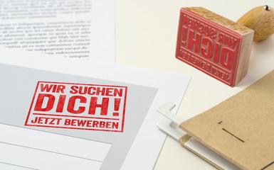 Roter Stempel auf Unterlagen - Wir suchen Dich
