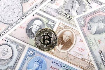 Bitcoin coin on the background of old Mexican banknotes