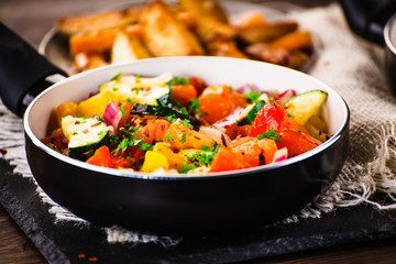 Vegetables and baked potatoes on wooden background