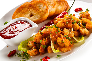 Grilled chicken nuggets and vegetables on white background
