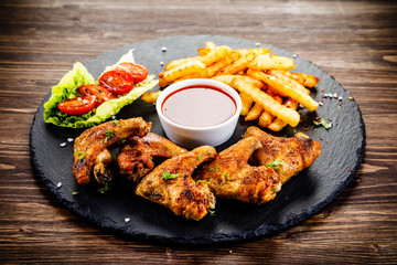 Grilled chicken wings, chips and vegetables