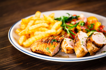 Grilled chicken fillet with french fries on wooden background