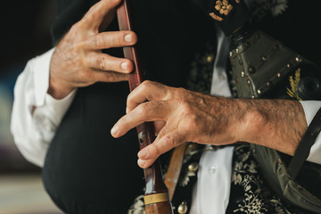 Older man plays bagpipes in folk costumes, close up