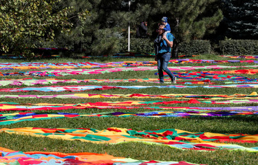 A man carries a child across a park decorated for the Apple Festival at City Day celebrations in Almaty