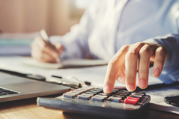 business man working in office and using calculator with pen