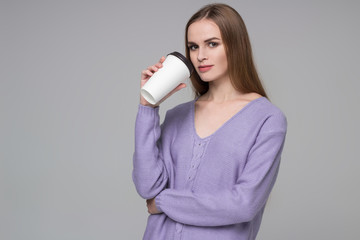 Girl in lilac jamper drinking coffee from paper plastic glass