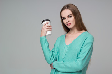 Girl in aquamarine jamper drinks coffee from paper plastic glass