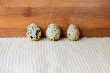 Three quail eggs stand in a row