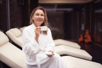 Nice thoughts. Portrait of attractive woman with wet hair sitting on daybed at spa salon with coffee. She is looking up with smile as if thinking about something good