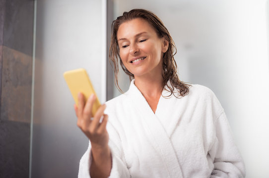 Happy news. Portrait of attractive woman in white soft bathrobe holding yellow cellphone and reading message from friend. She is standing near bathroom after taking shower