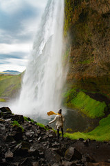 Woman stay on waterfall in Iceland, hide waterfall in Iceland, amazing sights and places to explore