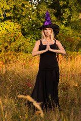 Glad female in Halloween costume practicing yoga