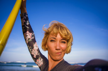 young attractive and happy blonde surfer woman in swimsuit holding surf board in the beach taking self portrait selfie picture smiling cheerful enjoying holidays