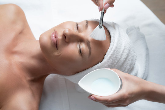 I am completely relaxed. Close up portrait of charming middle aged woman with closed eyes lying on massage table. Beautician hands holding bowl with clay and using cosmetic brush for applying mask on