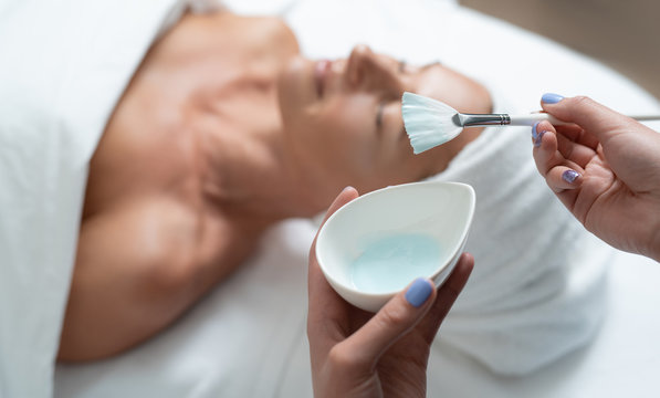 Almost ready. Cosmetologist hands holding bowl with cosmetic clay and brush. Lovely middle aged woman with closed eyes lying on massage table on blurred background