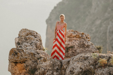 An attractive blonde woman in the red and white dress dancing on the top of the cliff with the mountain in the background. Mountain view. Evening in Spain
