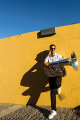 A young musician with a tuba stands on the street near the yellow wall.