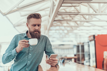 Portrait of concentrated bearded man drinking cup of coffee while typing in mobile indoor