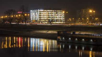 Obraz a bright office building by the river - fototapety do salonu