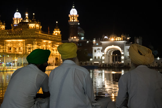 Three sikhs sitting at night in the Golden Temple, the most important temple and pilgrimage site of Sikhism, located in Amritsar, India.