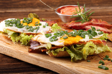 Fried eggs with bacon and chives on wooden background