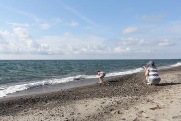 海辺で遊ぶ親子 母と娘 青い海と青空
