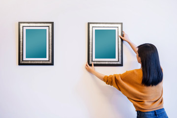 Photo Frame Mockup with Clipping Path. Woman Decorating a New House by Hanging the Blank Picture Frame on the Wall